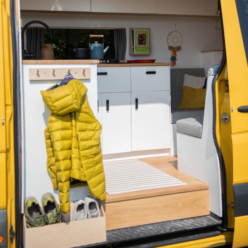 Well designed camper van kitchen with coat hooks and shoe rack