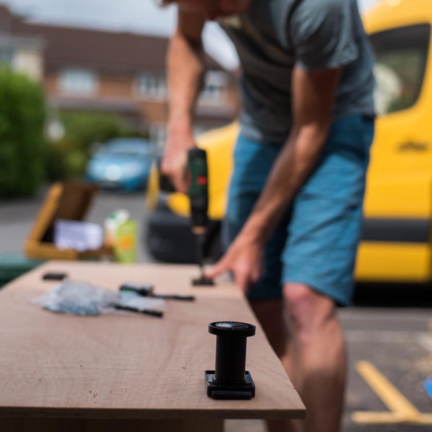 Man attaches IKEA feet to a camper van kitchen cabinet