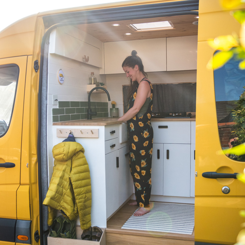 Woman washing up in a Belfast sink in a beautiful kitchen in a campervan conversion