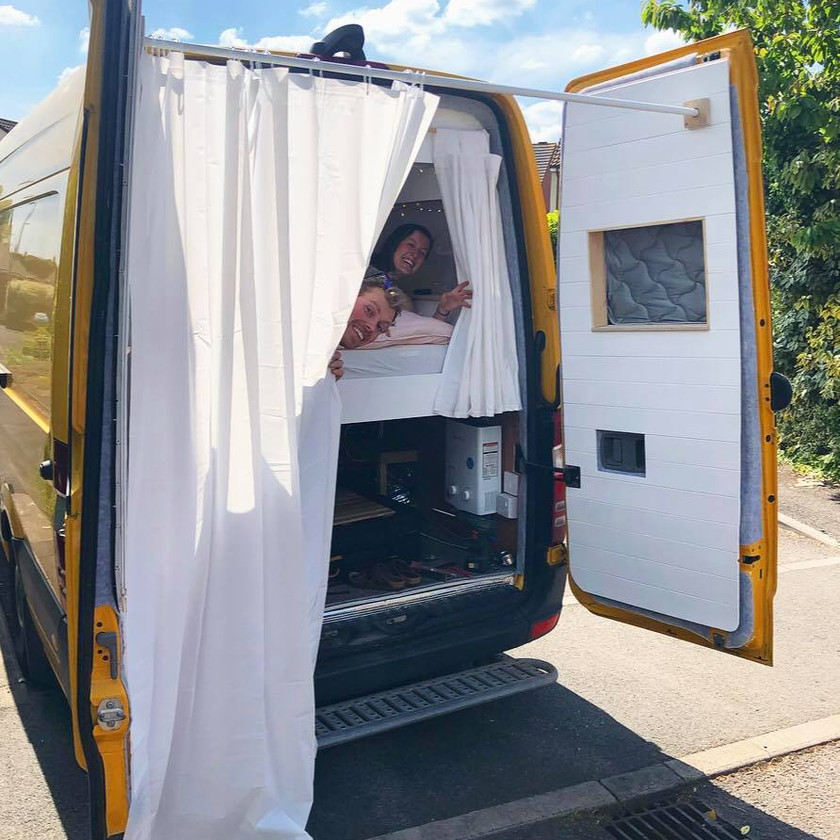Couple peer around an outdoor shower setup in a Mercedes Sprinter camper van conversion