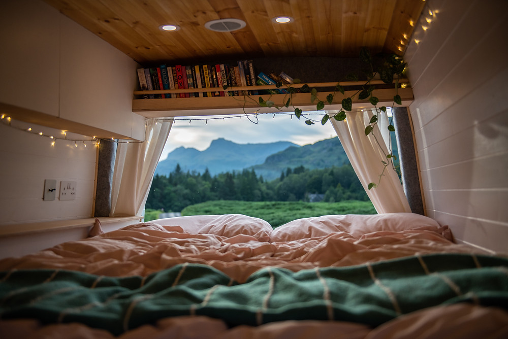 Beautiful self build campervan conversion bed with bookcase and view of mountains in Lake District