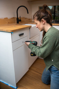 Girl fits door handles to a kitchen cabinet inside a camper van conversion with a Belfast sink