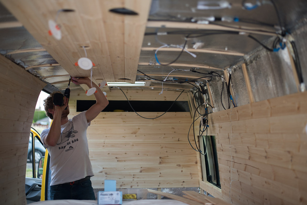 Man attaches cladding to the ceiling of a Sprinter camper van conversion