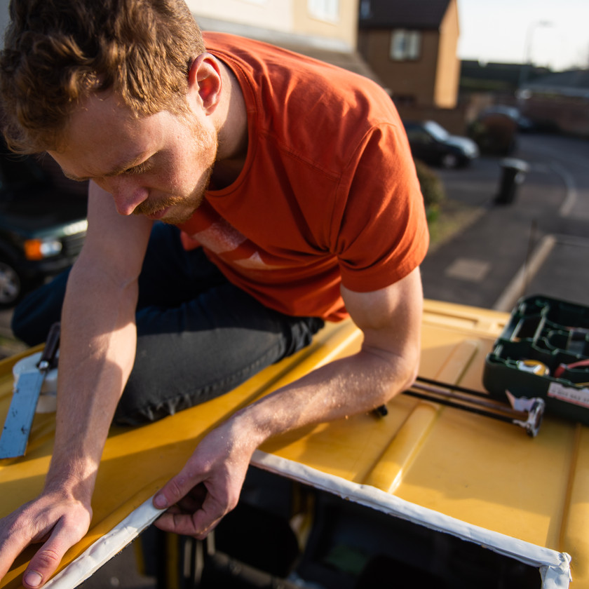 man applying Mastic tape to a van conversion in order to install a skylight
