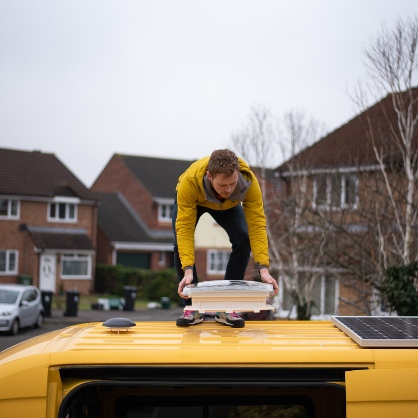 man installing a Dometic skylight on a Sprinter van conversion