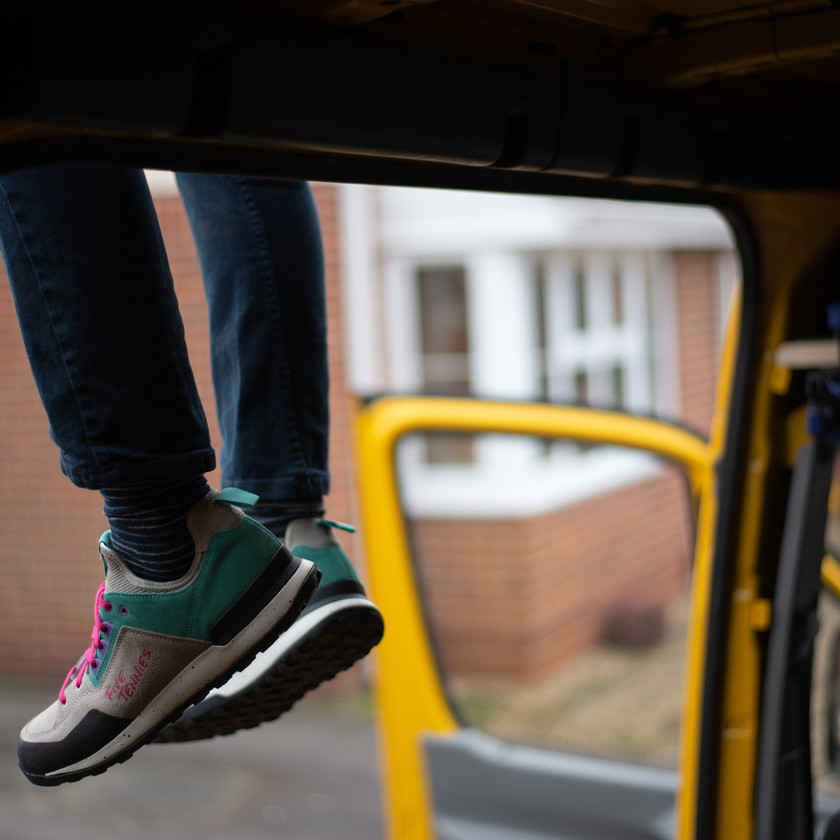 man's legs dangling from the roof of a yellow Sprinter campervan