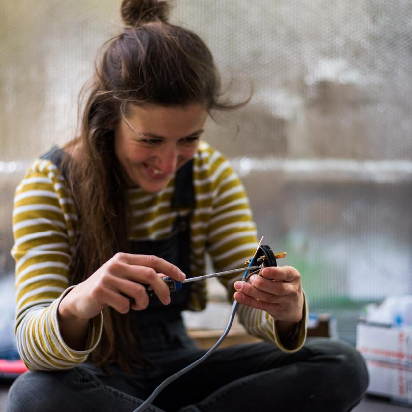 girl wiring a plug socket in a camper van electrical system