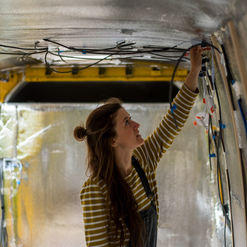 Girl wiring 12V lights into a van conversion electrical system