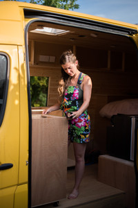 Girl measures out a self build camper van kitchen