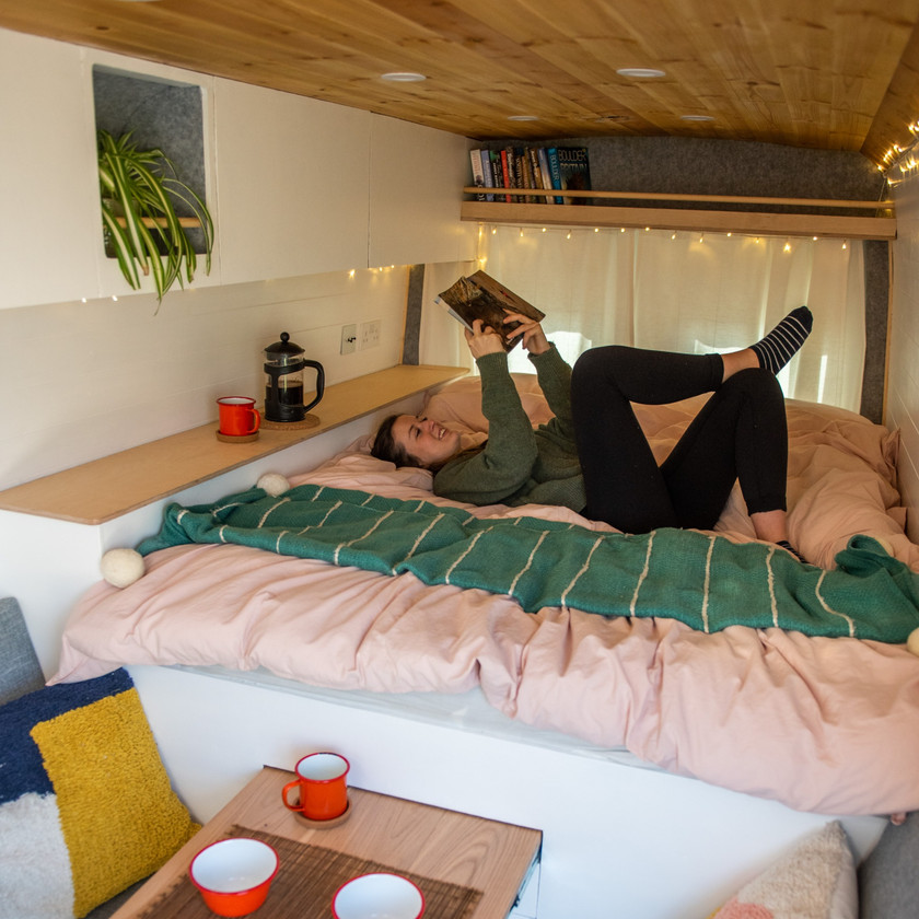 Girl lounges on a bed reading in a beautiful modern Scandi style camper van conversion