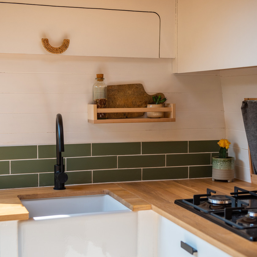 A Belfast sink and IKEA spice rack and green ceramic tiles in a camper van conversion kitchen
