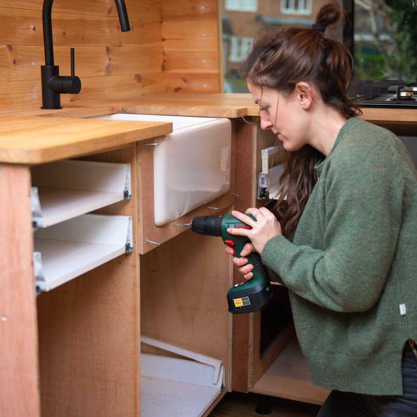 Girl fits a Belfast sink into a Sprinter camper van conversion