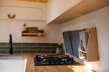Beautiful wooden birch ply book case in a Scandi camper van kitchen