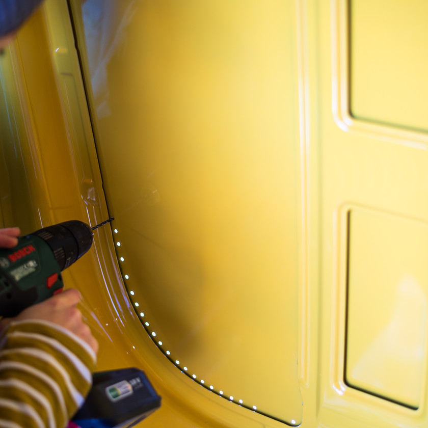 girl drilling holes in the side of a van conversion in order to install windows