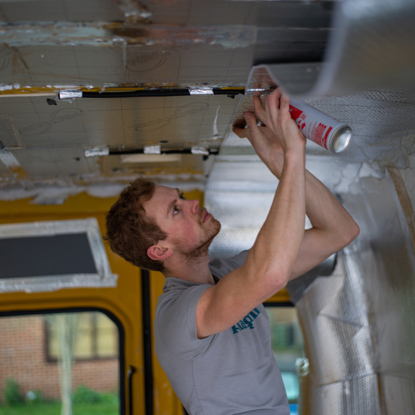 man applying ThermaWrap silver foil bubble wrap insulation to a van conversion using spray adhesive glue