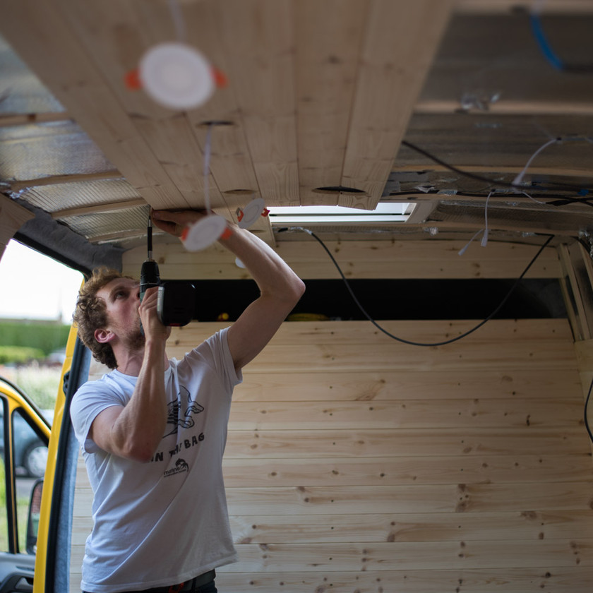 Man installs cladding in the ceiling of a Sprinter van conversion