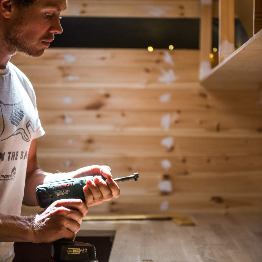 Man holding drill ready to cut a hole in a camper van worktop to fit a hob