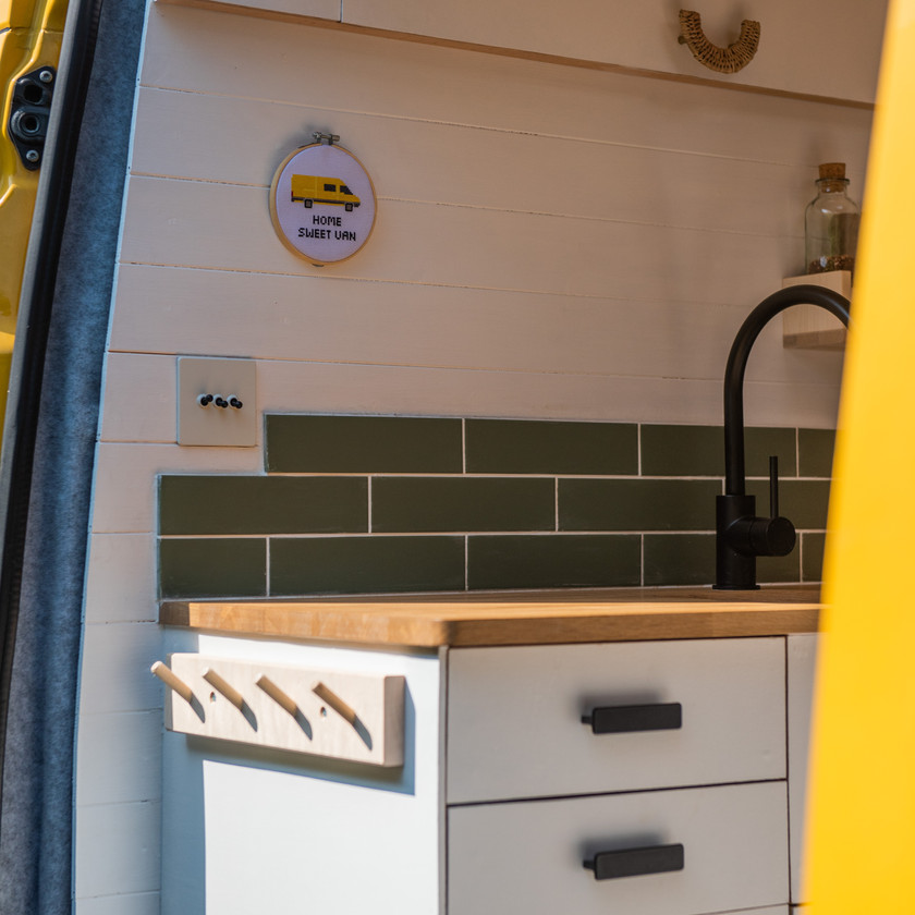 Cross stitch and coat hook details in a Sprinter camper van conversion kitchen layout