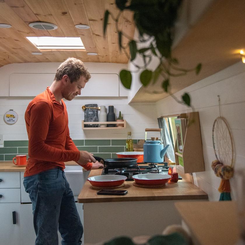 Man cooking in a campervan van conversion kitchen