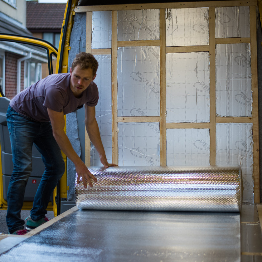 man rolling ThermaWrap silver foil bubble wrap insulation onto a van conversion floor