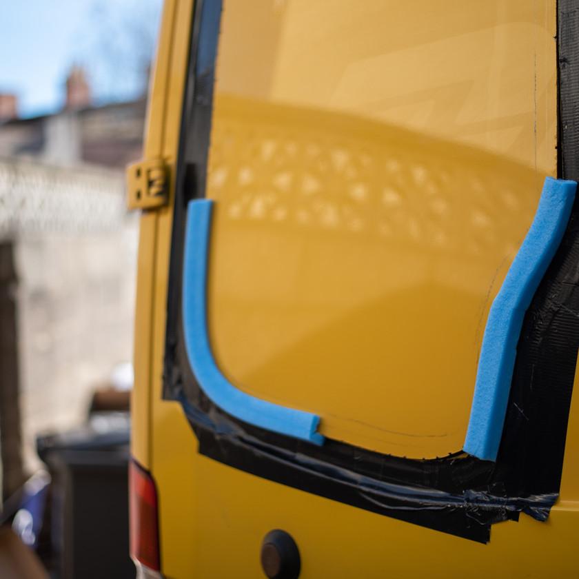 cutting windows into a yellow Sprinter van conversion