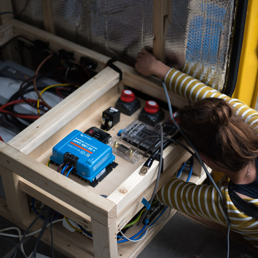 Girl connecting up a van electrical system, including an MPPT charge controller and 12V fuse box