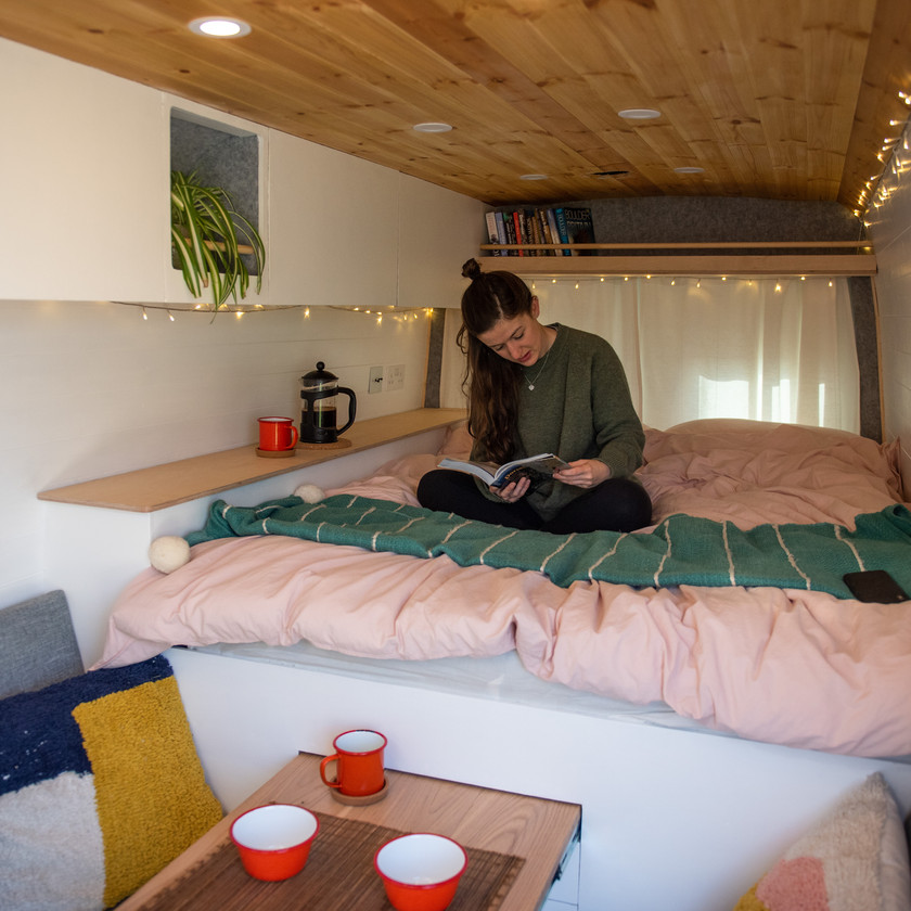 Big bed and living seating area inside a Mercedes Sprinter camper van conversion