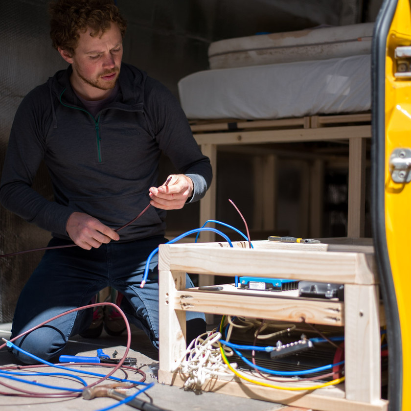 Man wires in a camper van electrical system