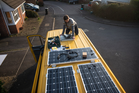 Girl sat on the roof of a yellow Mercedes Sprinter installing solar panels on a van conversion