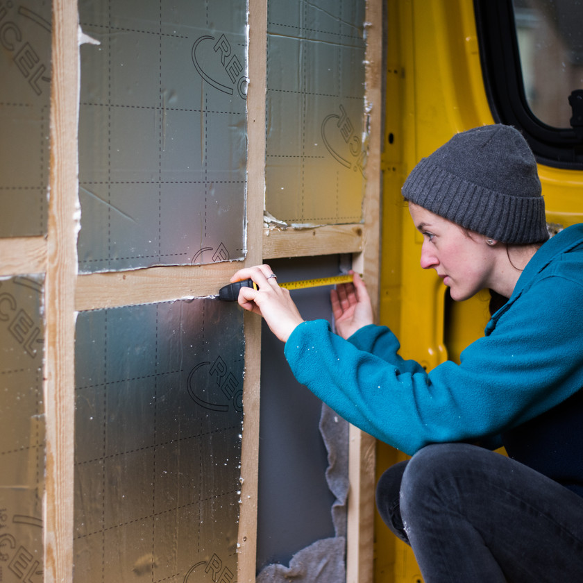 girl measuring space in van studwork for Recticel thermal insulation board