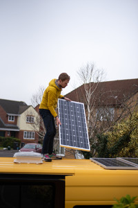 Man installing a solar panel onto the roof of a Mercedes Sprinter camper van