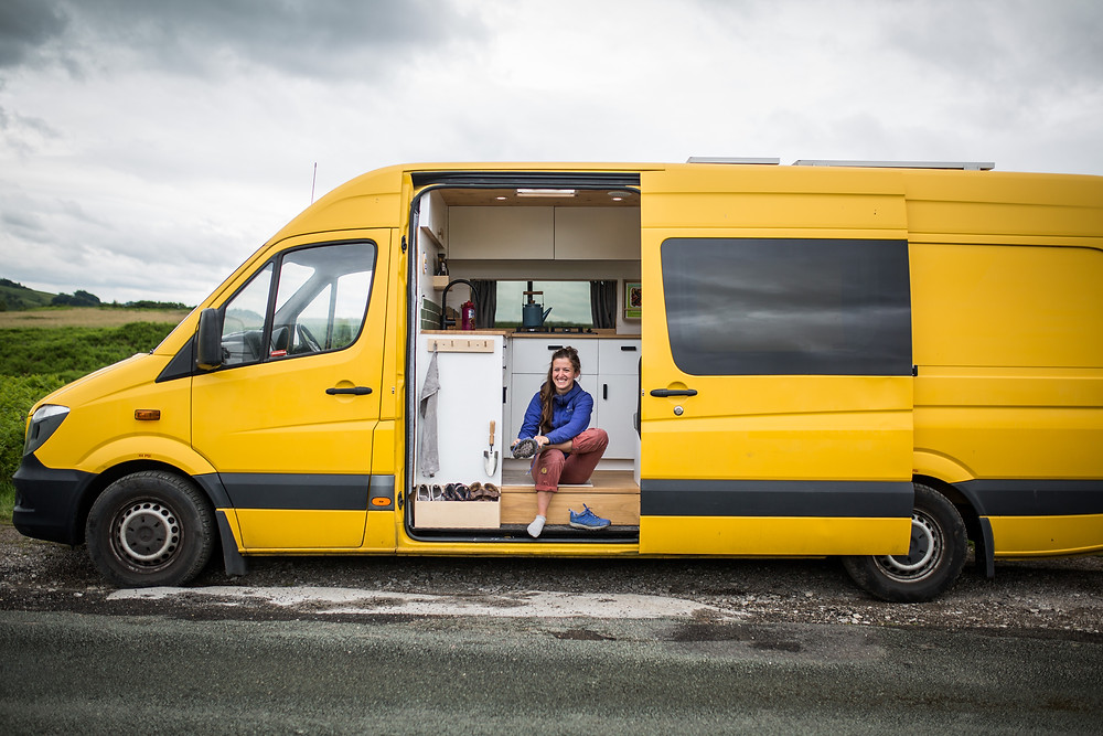 Girl puts her shoes by a campervan kitchen inside a large yellow Sprinter van conversion