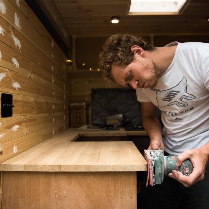 Man sanding camper van worktop in kitchen