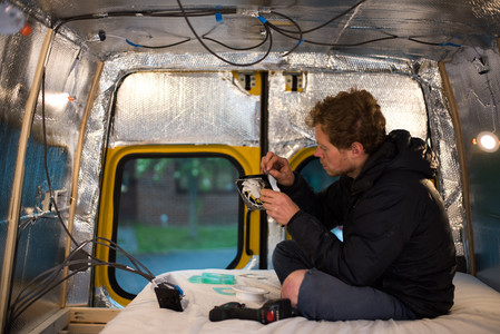 Man wiring a 12V computer fan into a campervan electrical system to use as a vent