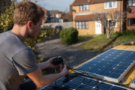 man wiring up Renogy solar panels on the roof of a Sprinter van conversion