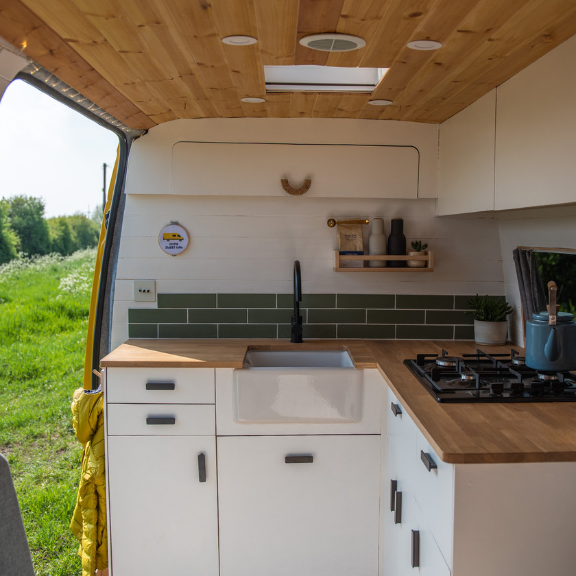 Beautiful well designed camper van kitchen with ceramic tiles and Belfast sink, white scandi wood aesthetic