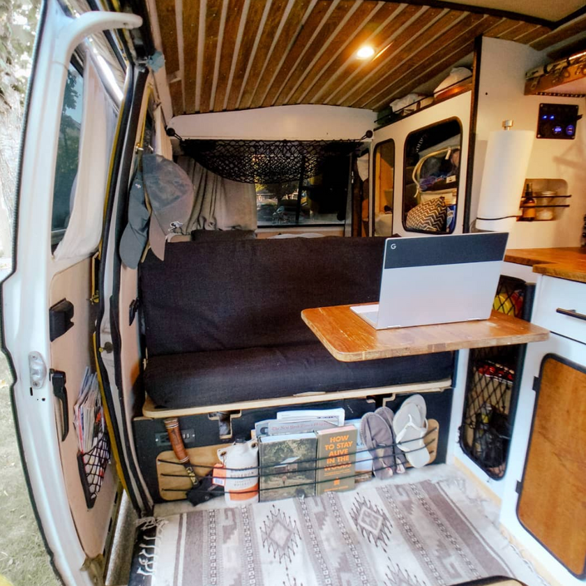 Kitchen, rock and roll bed and fold out table in a VW Transporter T3 camper van conversion