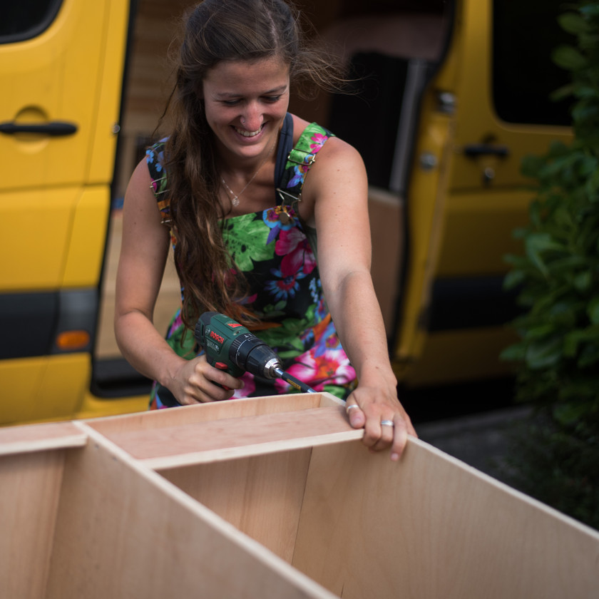 Girl builds camper van kitchen units with power drill