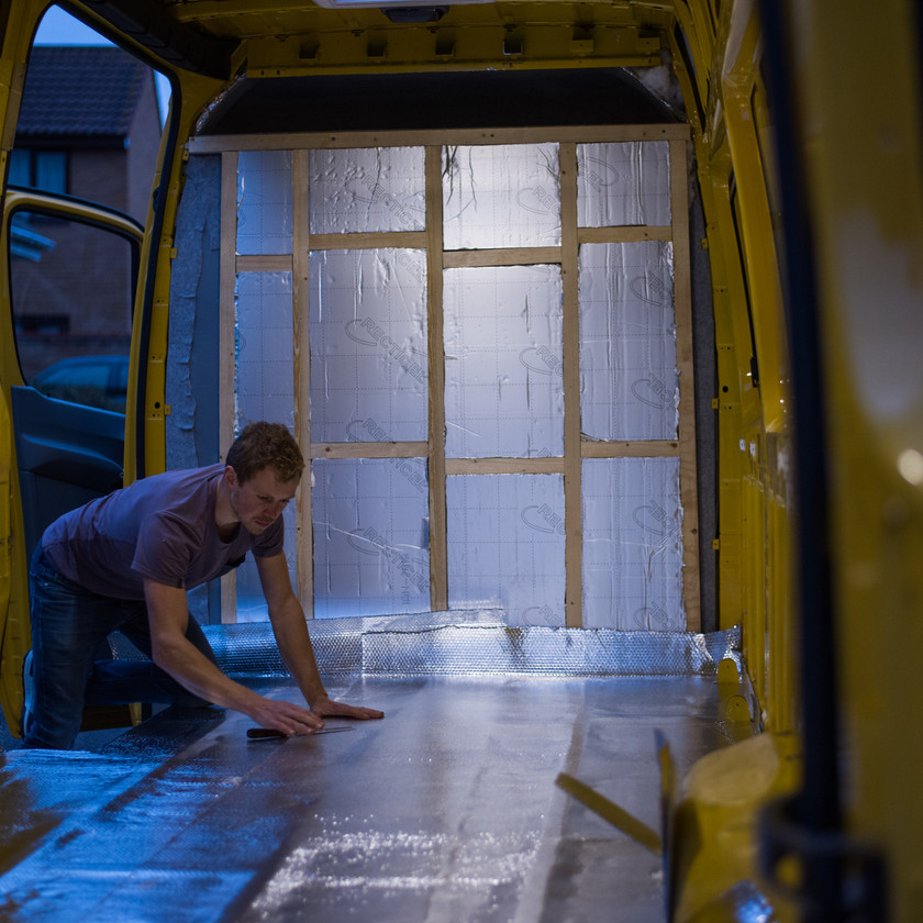 Man insulates a Sprinter van conversion with silver foil bubble insulation