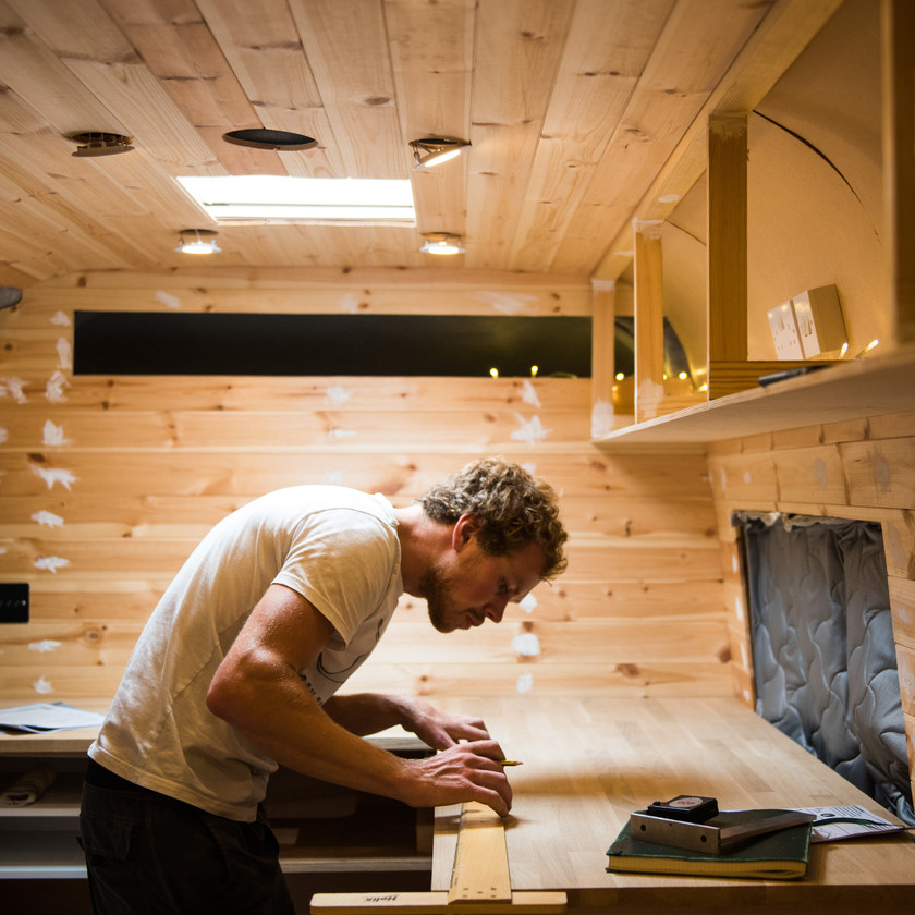 Man measure worktop in camper van kitchen