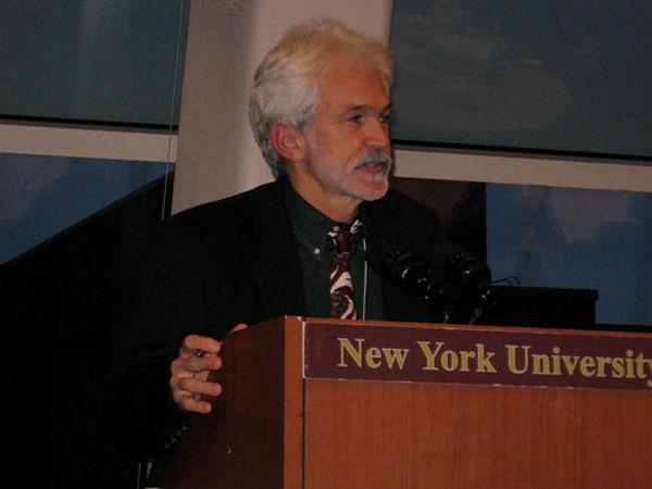 Ein Mensch an einem Pult. Auf dem Pult steht: New York University