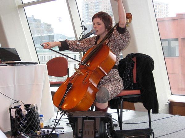 Ein Mensch sitzt auf einen Stuhl und spielt ein Cello