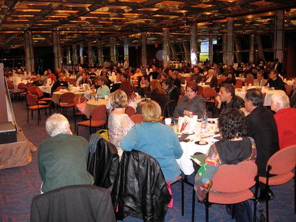 Viele Menschen an Tischen in einem großen Saal