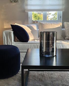 Weißes Sofo hinter schwarzem Couchtisch mit Vase