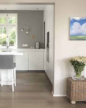 Blick in weiße Kueche mit Fenster und grauer Wand