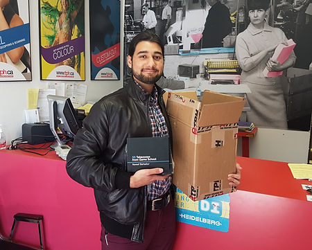Nawaf holdng first print of his book, 55 Things I learned In Game School