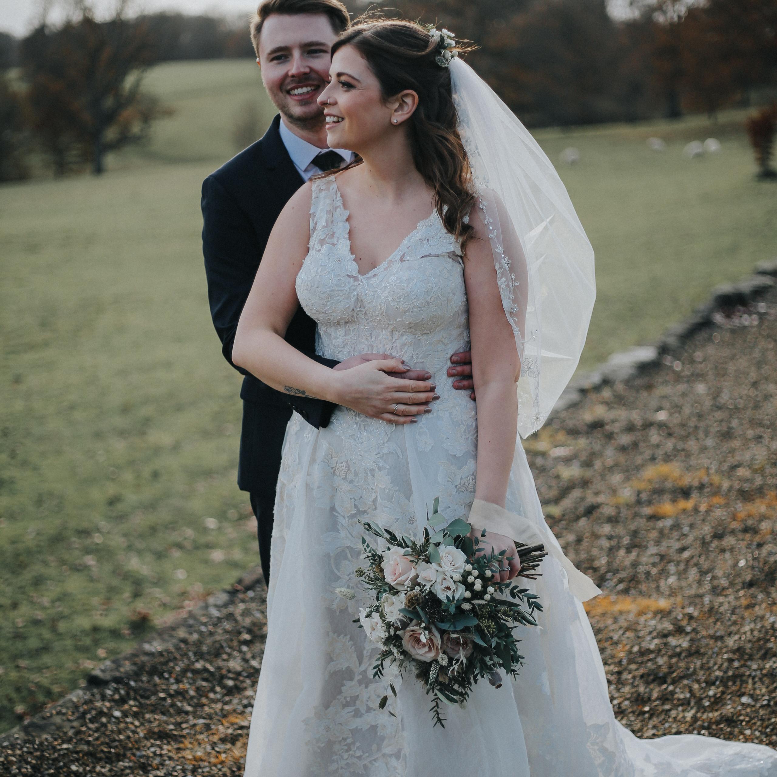 Bride and groom look nonchalantly across wedding grounds of Wadhurst Castle