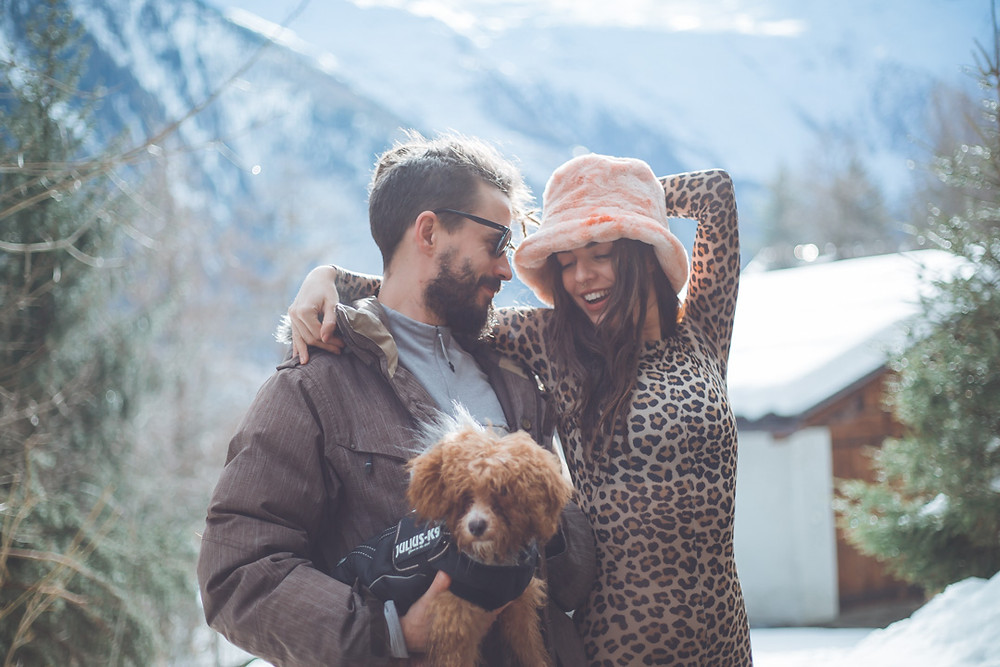 Couple portrait with dog in front of the mountains in Chamonix