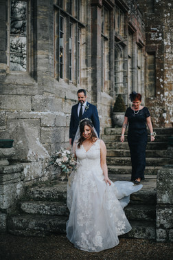 Bride walks down stairs on her way to the alter with mother and father at Wadhurst Castle