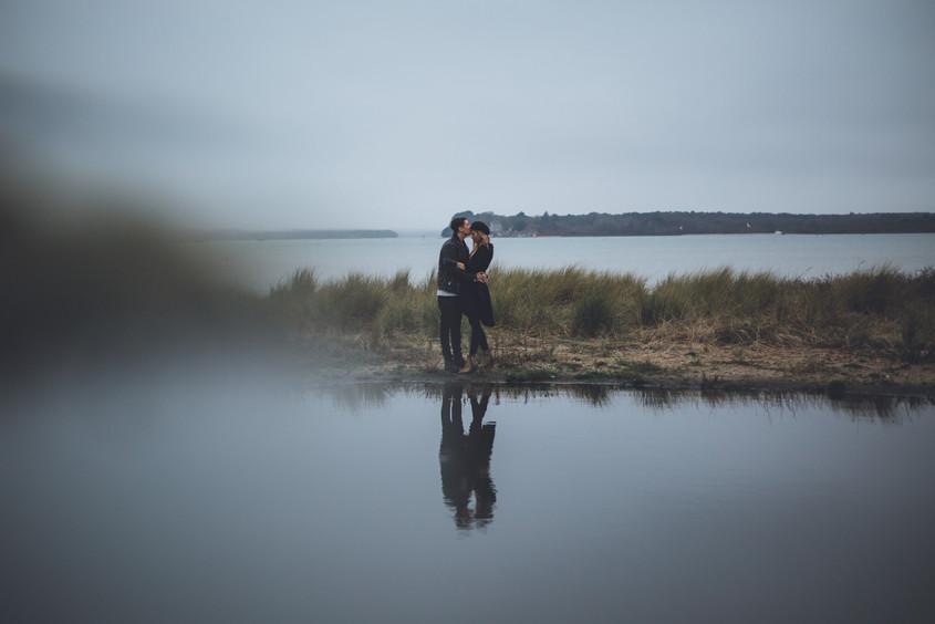 photo by wedding photographer of man kissing woman on head during couples shoot on Sandbanks beach